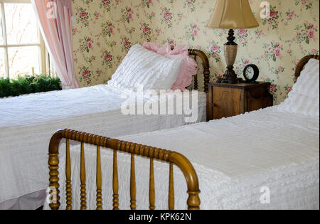twin beds with white bedspreads in bedroom with retro floral wallpaper - Stock Photo