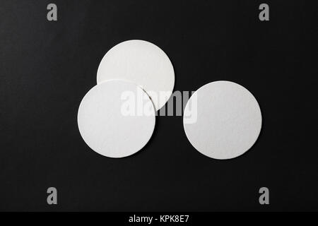Three blank beer coasters on black paper background. Flat lay. - Stock Photo