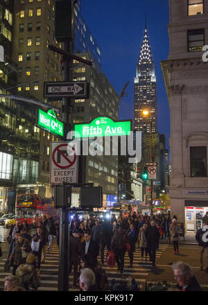 During the Christmas holiday season the streets of Manhattan are extra busy day and night. Looking across 5th Avenue, - Stock Photo