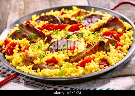 Serving of speciality Spanish Al Homo paella with spare ribs and black pudding on savory rice with red peppers served - Stock Photo
