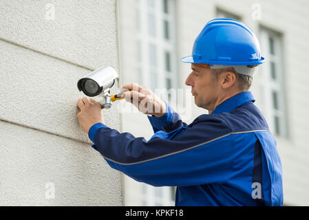 Mature Technician Installing Camera On Wall With Screwdriver - Stock Photo