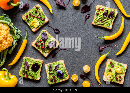 Breakfast different avocado sandwich. Different Fresh colorful organic vegetables. healthy raw vegan food on grey - Stock Photo