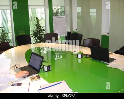 office worker works on laptop in modern office - Stock Photo
