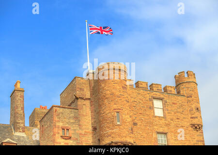 Close up of the tower of the Castle of Mey with british flag located on north coast of the Highlands in Scotland, United Kingdom on a blue sky.