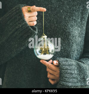 Woman in grey sweater holding decorative glass ball, square crop - Stock Photo