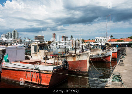 Classic Red Fishing Boats moored in front of the yachts of the rich people in Punta del Este harbor, Uruguay - Stock Photo