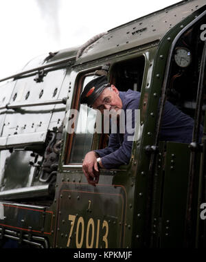 The driver of preserved British Railways Standard Class 7 steam locomotive no. 70013 Oliver Cromwell leaning out - Stock Photo