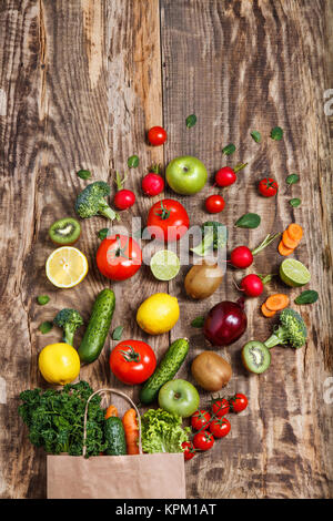 The vegetables from a paper bag on wooden table - Stock Photo