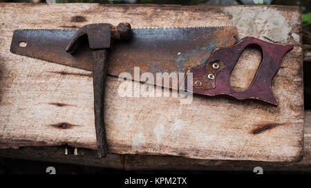 Old rusty tools hammer and hand saw for carpenter work - Stock Photo