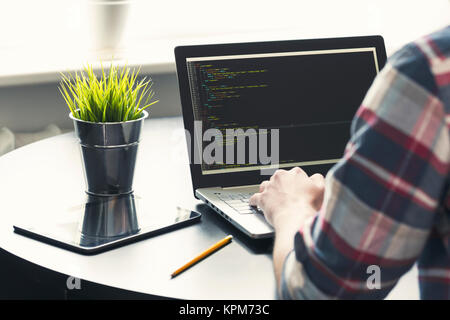 programmer working on laptop at office. focus on programming code - Stock Photo