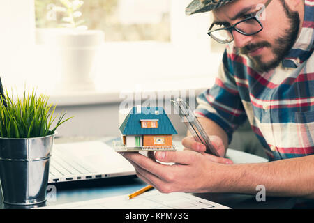 architect, construction engineer taking measurements of new house project at office - Stock Photo