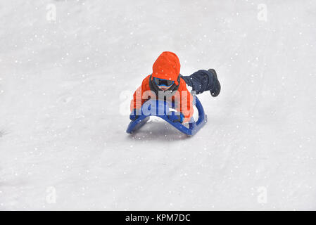 Little boy riding on snow slides in winter time - Stock Photo