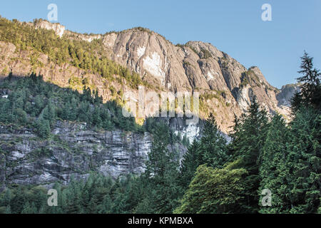In Princess Louisa Inlet, morning sun lights up the mountain tops along the west shore, while lower elevations are - Stock Photo