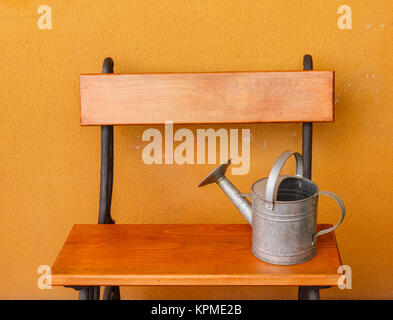 a watering-can  aluminium laid on a wooden bench - Stock Photo