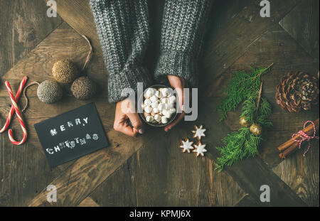 Flat-lay of greeting card, woman's hands in sweater holding mug - Stock Photo
