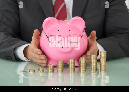 Businessman Covering Piggy Bank With Stacked Coins At Desk - Stock Photo