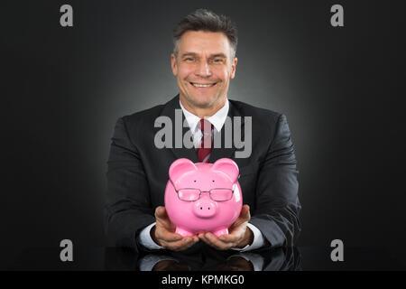 Businessman Sitting And Holding Piggybank - Stock Photo