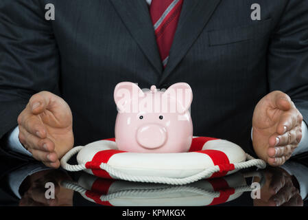Close-up Of Businessman Hand Protecting Piggybank With Lifebelt - Stock Photo