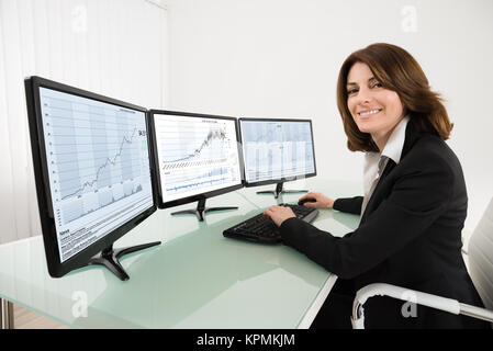 Female Stock Market Broker Working On Multiple Computers - Stock Photo