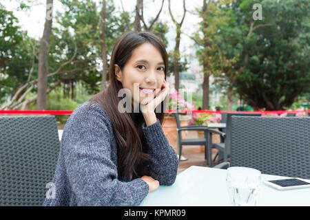 Asian Woman in outdoor restaurant - Stock Photo