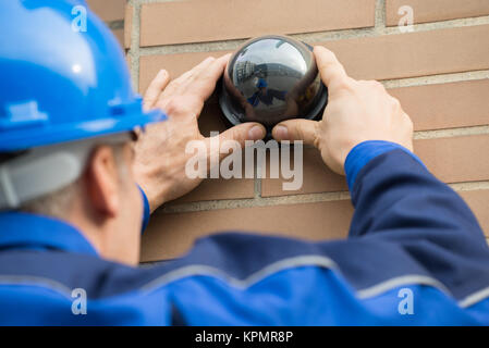 Close-up Of Technician Installing Camera In Building - Stock Photo