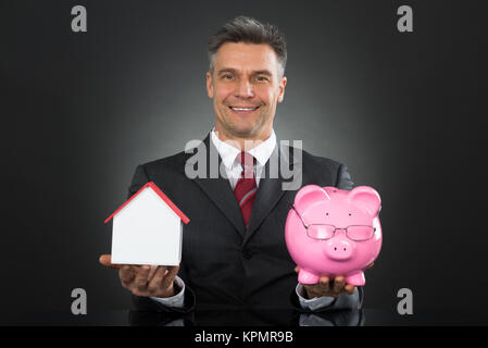Businessman Holding Piggy Bank And House Model - Stock Photo