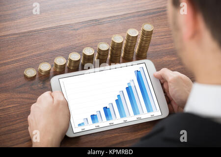 Businessman Analyzing Financial Graph On Digital Tablet - Stock Photo