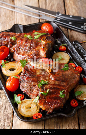 Delicious T Bone steak with grilled vegetables on the grill pan close-up on the table. vertical - Stock Photo