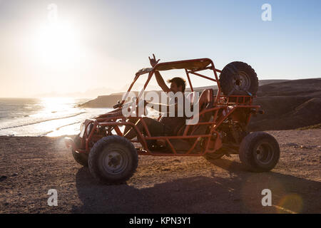 Man driving quadbike in sunset. - Stock Photo