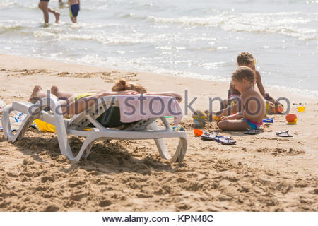 On the sea beach near the water with sunbathing chaise longue Woman and children playing in the sand - Stock Photo