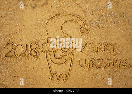 Handwriting words MERRY CHRISTMAS 2018 on sand of beach and funny face of santa claus. - Stock Photo