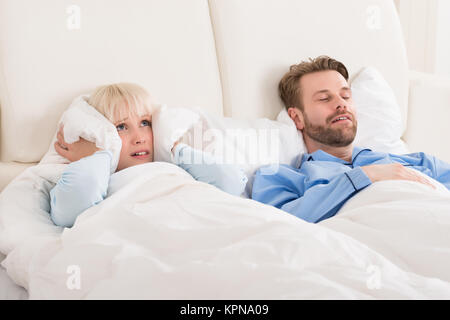 Woman Covering Ears While Man Snoring In Bed - Stock Photo