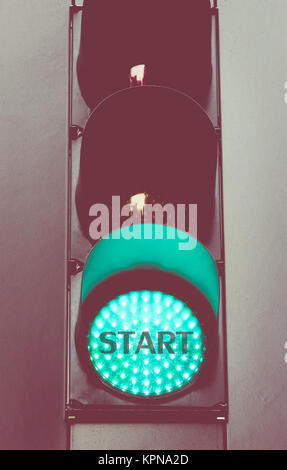 Close up on green traffic light with message START - Stock Photo