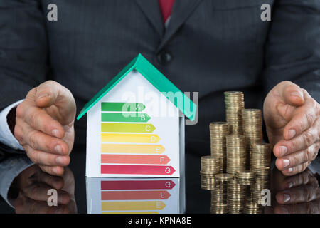 Businessperson Protecting House Model Stack Of Coins - Stock Photo