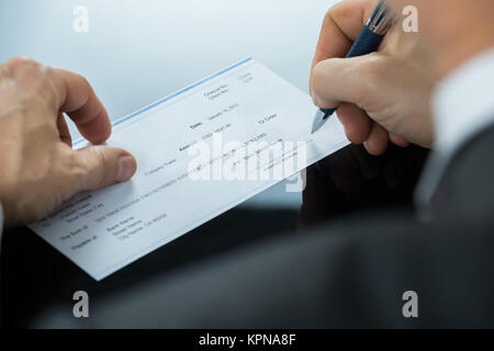 Close Up Of Businessman Filling Blank Cheque At Desk - Stock Photo