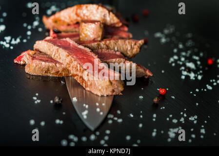 Closeup of medium rare steak slices on a knife - Stock Photo