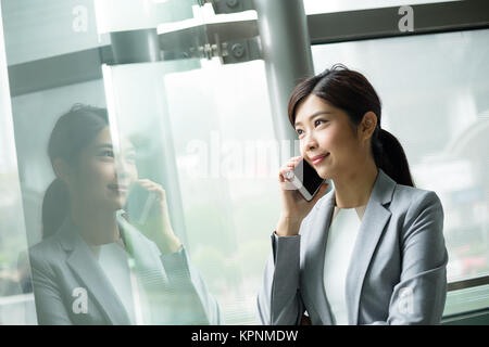 Businesswoman talk to cellphone inside office - Stock Photo