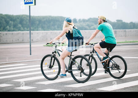 Couple of romantic lovers cycling people, love, nature and lifestyle concept - Stock Photo