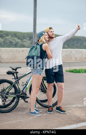 loving couple is taking a selfie on their smartphone in the city center - Stock Photo
