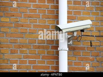 Surveillance Camera mounted on Yellow Brick Wall - Stock Photo