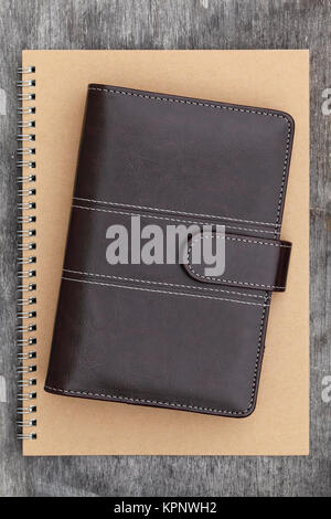 brown leather organizer and spiral notebook - Stock Photo