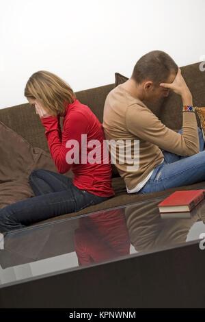 Model release , Symbolbild Beziehungsprobleme, Frau und Mann sitzten Ruecken an Ruecken auf einer Couch - symbolic - Stock Photo