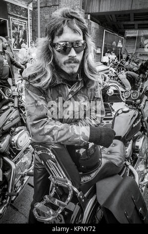 Biker with long hair and mirror sunglasses leans on his bike in Hungerford. Scenes from the Harley Davidson rally - Stock Photo