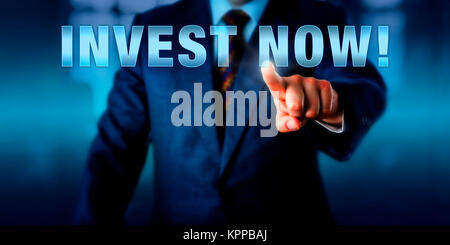 Financial Advisor Touching INVEST NOW! - Stock Photo