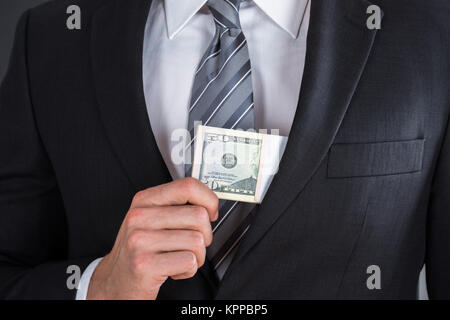 Businessman Putting Bribe In Suit Pocket - Stock Photo
