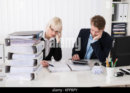Businesspeople Calculating Invoices - Stock Photo