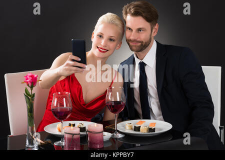 Young Couple Taking Selfie With Their Smartphone - Stock Photo