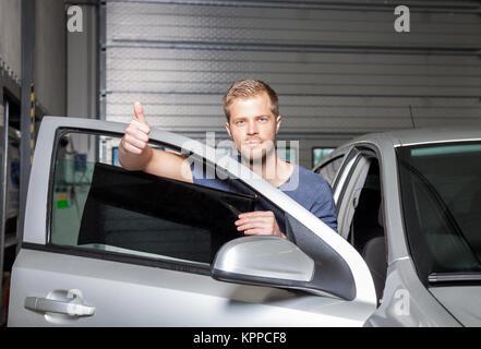 Applying tinting foil onto a car window - Stock Photo