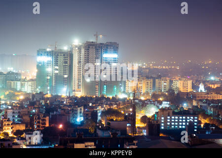 Skyscapers under construction in the middle of the smaller residences and offices that make up the city of noida - Stock Photo