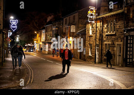 Bridge street Otley night scene showing a gentleman dressed in Victorian clothes and a romantic couple kissing and - Stock Photo